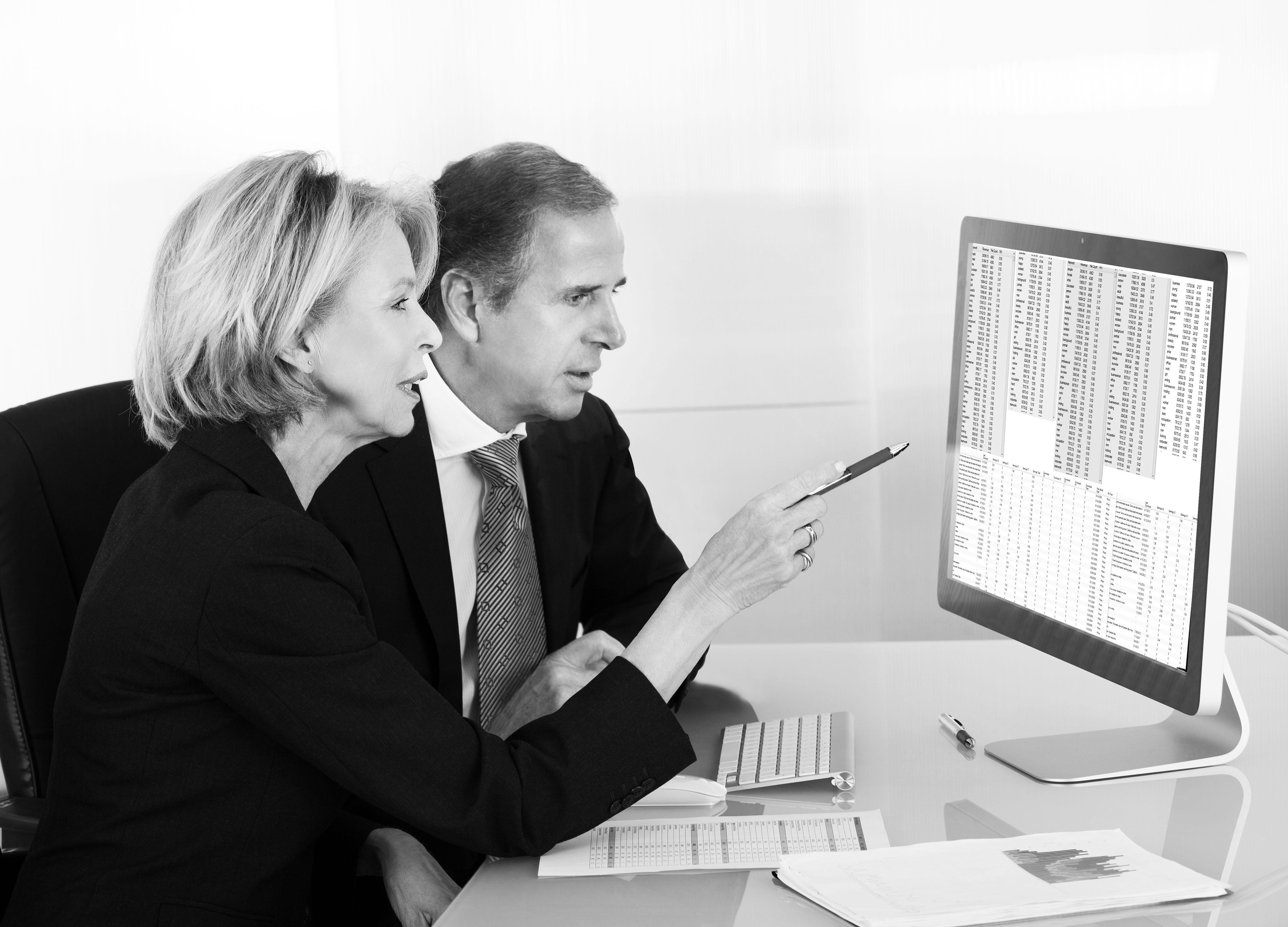 Dame og mann som ser på regnskapstall på skjerm.